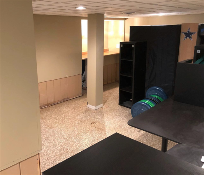 Basement with water damage to floors and walls