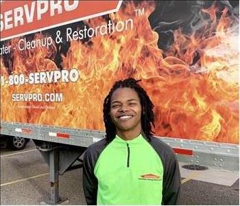 Male SERVPRO employee smiling in front of SERVPRO semi