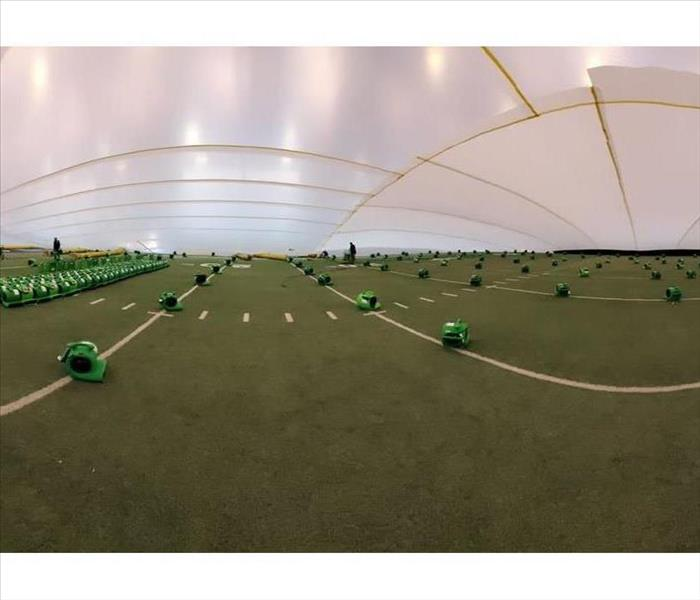 Drying equipment on indoor football field that was damaged by flood