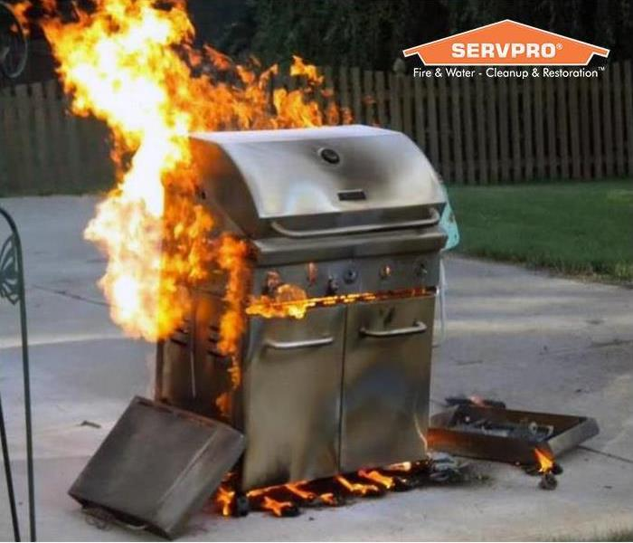 Grill on fire with SERVPRO logo