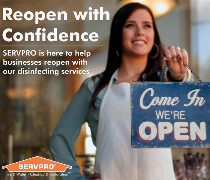 Lady holding open sign with SERVPRO logo