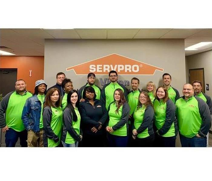 Employees wearing green SERVPRO pullovers smiling in front of SERVPRO logo