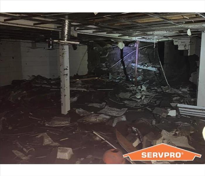 Flooded basement with severe damage and SERVPRO logo